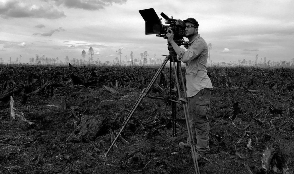 Mario Hötschl mit Kamera in abgebranntem Wald